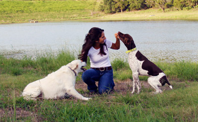 Destiny Valladares ineracting with two ranch dogs